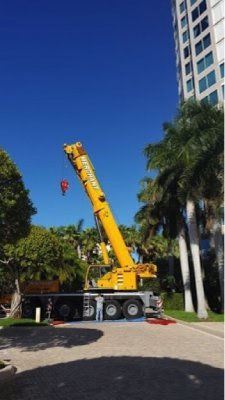 """The crane boom began to be assembled briefly blocking the entrance to the parking garage. Sheets of plywood were hoisted up to the terrace of the penthouse to protect the tiled flooring of the """"landing spot."""""""