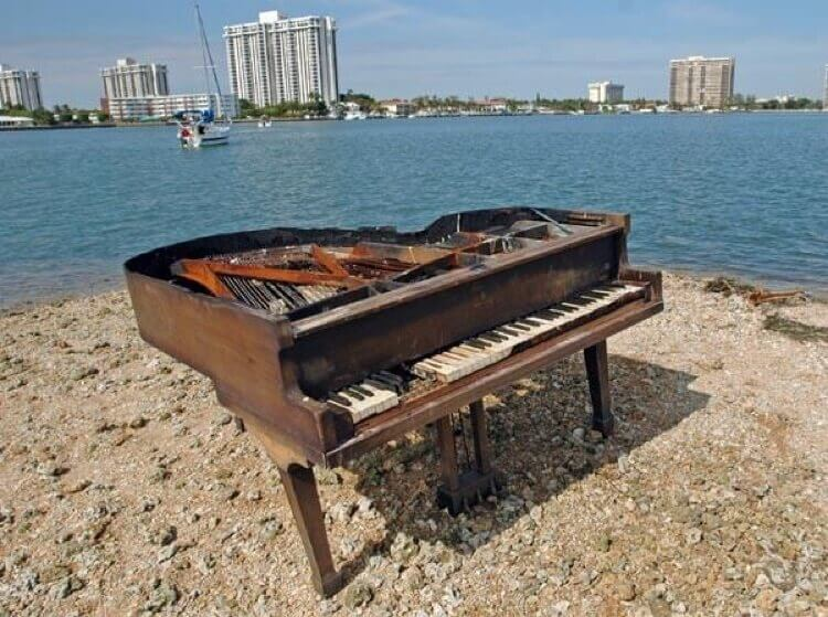 damaged baby grand piano on the beach in Miami
