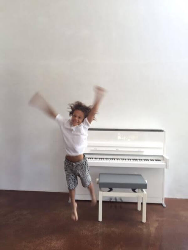 A new student overjoyed with her white Schimmel upright purchased from Euro Pianos Naples.